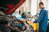 Photo Mechanic pumps freon into the car air conditioning system. Conditioner inspection in auto-service