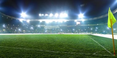 Football stadium, corner flag, shiny lights, view from field grass. Turf, nobody on playground, tribunes with game fans on background