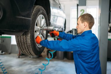 Mechanic unscrews the wheel with a pneumatic wrench. Car service, automobile repair, vehicle maintenance