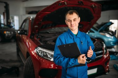 Technician with notebook standing against a car with opened hood, repairman fixing the problems. Automobile service, vehicle maintenance