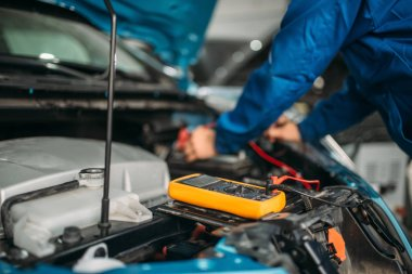 Car electrician with multimeter checks the battery level. Auto-service, vehicle wiring diagnostic