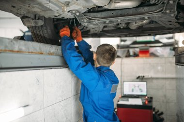 Mechanic adjusts the wheel angles on stand in auto-service. Computer diagnostic of car suspension, collapse of convergence