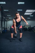 Fotografie Silný muž sportovní dělat cvičení s kettlebell, vzpírání. Vzpírání cvičení, sportovec sportovní nebo fitness clubu, zvedák na tréninku v tělocvičně
