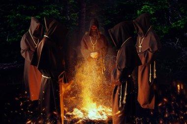 Gece, gizli tören büyük bir yangında karşı dua ortaçağ keşiş. Karanlık pelerinli gizemli rahip. Gizem ve Maneviyat
