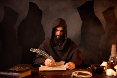 Medieval monk in robe makes notes in the secret scripture with a goose feather, black background, secret ritual. Mysterious friar in dark cape. Mystery and spirituality