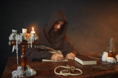 Medieval monk sitting at the table and writes with a goose feather, top view, secret scripture. Mysterious friar in dark cape. Mystery and spirituality