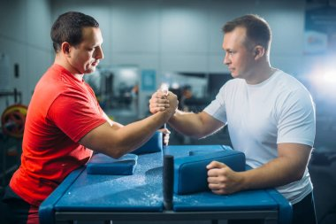 Two arm wrestlers prepares for the battle at the table with pins, workout before wrestling competition. Wrestle challenge, power sport