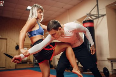 Female person practicing a knee kick to the stomach on self defense workout with male personal trainer, gym interior on background. Woman on training, self-defense practice