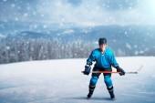 Jeden hokejista s holí na otevřené ledové, herní koncept, zasněženého lesa na pozadí. Mužské osoby v přilbu, rukavice a v ochranné jednotné venku, Zimní sportovní hry
