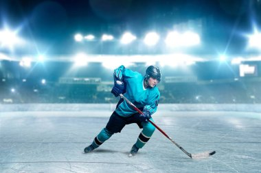 One hockey player skating with stick on ice arena, spotlights on background. Male person in helmet, gloves and uniform playing game