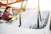 Žena na myček, myčka procesu. Venkovní vozidlo mytí v letním dni. Ženská osoba s houbou vyčistí automobil čelní sklo
