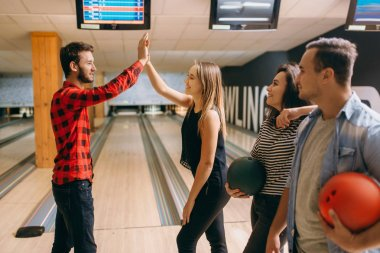 Bowler throws ball on lane and makes strike shot. Bowling alley team congratulates each other, successful throwing. Men and women playing the game in club, active leisure