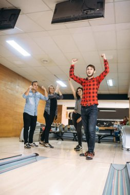 Male bowler cheers holding hands up, he just makes strike shot. Bowling alley team congratulates each other, successful throwing. Men and women playing the game in club, active leisure