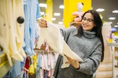 Happy future mother choosing clothes in the store for newborns. Pregnant woman in shop of goods for infants