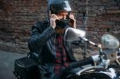 Fotografie Biker klade na helmu před jízdou na klasickém vrtulníku. Retro kolo jezdec na motocyklu