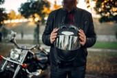 Muž motorkář drží helmu v rukou, klasické chopper na pozadí. Retro kolo, silniční jezdec a jeho motocykl, svoboda životní styl, cykloturistika