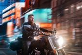 Motorkářská jízda na vrtulník přes noční město, blured panoráma a reklamy s neonová světla na pozadí. Vintage kolo, jezdec na motocyklu, asfalt silniční dobrodružství, svobodu životní styl