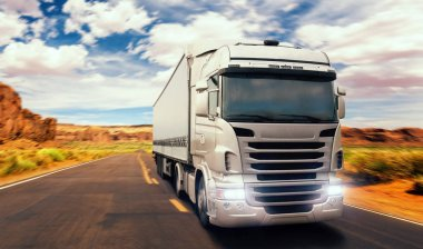 Freight truck on road in valley, front view. Heavy traffic on the freeway, transportation and logistic concept, truckers lifestyle, long vehicle