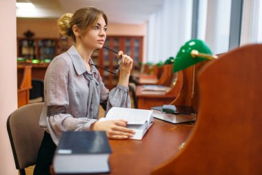 Female student learning book in university library. Woman studying in knowledge depository, education
