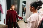 Dvě ženy výběr oblečení, nákupy. Shopaholics v obchod s oblečením, konzumní životní styl, móda