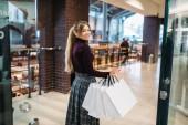 Fotografie Mladá žena s nákupní tašky v obchoďáku. Obchod s oblečením, konzumní životní styl, móda, atraktivní dáma, Nakupování v obchodě shopaholic