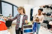 dvě mladé atraktivní ženy nakupování, dámského spodního prádla. Shopaholics v obchod s oblečením, konzumní životní styl, móda, Žena nakupujících s taškami