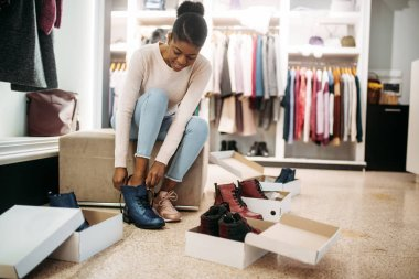 Black female person trying on shoes, shopping. Shopaholic in clothing store, consumerism lifestyle, fashion