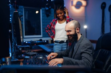 Sound engineer and female singer at remote control panel in audio recording studio. Musician in headphones listens composition, professional music mixing stock vector