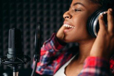Female singer in headphones songs in audio recording studio. Musician listens composition, professional music