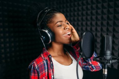 Female singer in headphones songs in audio recording studio. Musician listens composition, professional music mixing