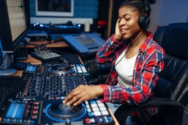 Female sound operator working at the remote control panel in audio recording studio.  Musician at the mixer, professional music mixing