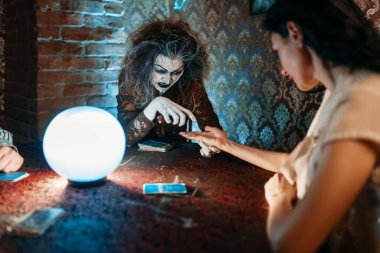 Female foreteller guessing by hand over a crystal ball, witchcraft. Scary witch reads a magic spell, young woman on spiritual seance