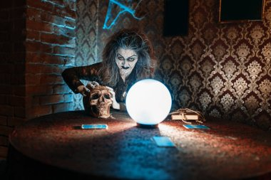 Scary witch with human skull reads a magic spell over a crystal ball, young people hands up on spiritual seance. Female foreteller calls the spirits