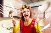 Verrückte Hausfrau in Kochschürze, herumfliegendes Kochgeschirr, Kücheneinrichtung im Hintergrund. Verrückte Frau mit Geschirr