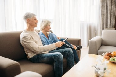 Mature couple sitting on couch and watching TV, happy family. Adult husband and wife resting at home