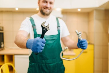 Plumber in uniform holds wrench, handyman. Professional worker makes repairs around the house, home repairing service