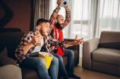 Zwei männliche Fußball Fans Wathing Fernsehen zu Hause. Freunde mit Bier und Popcorn für ihre Lieblingsmannschaft anfeuern