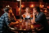 Fotografie Zwei Männer Treppen an die üppigen Brüste der Kellnerin im Pub, Oktoberfest Reisen. Männliche Person trinken in der bar, Bardame im klassischen retro-Stil