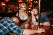 Fotografie Zwei betrunkene Freunde schlafen an der Theke mit Bierkrüge im Pub, hübsche Kellnerin auf Hintergrund, Oktoberfest Reisen. Männliche Personen trinken in der bar, Bardame im klassischen retro-Stil