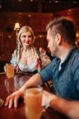 Fotografie Betrunken Mann mit Bierkrug und hübsche Kellnerin an der Theke im Pub, Oktoberfest Reisen. Männliche Person trinken in der bar, Bardame im klassischen retro-Stil