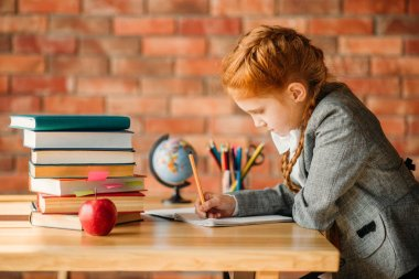 Cute schoolgirl doing homework at the table with textbooks, apples and globe. Female pupil reading a book at the desk
