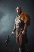 Vikingové se sekyrou, bojovým duchem, barbarským obrazem, výhledem z boku. Starověký bojovník v dýmu na tmavém pozadí
