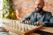 Photo Male chess players begin playing, focus on board with figures. Two chessplayers begin the intellectual tournament indoors. Chessboard on wooden table, strategy game