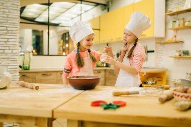 Two little girls cooks in caps tastes sweet vanilla powder, cookies preparation on the kitchen. Kids cooking pastry, children chefs preparing cake
