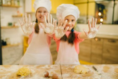Two little girls cooks in caps shows hands covered in flour, cookies preparation on the kitchen. Kids cooking pastry, children chefs preparing cake