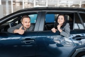 Happy couple sitting in new car, showroom. Male and female customers choosing vehicle in dealership, automobile sale, auto purchase