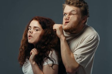 Young couple faces crushed on transparent glass, funny emotion. Man and woman with pressed grimaces standing at the showcase, humor, uncomfortable looking