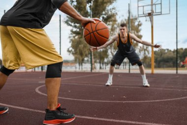 Two basketball players work out tactics on outdoor court. Male athletes in sportswear play the game on streetball training