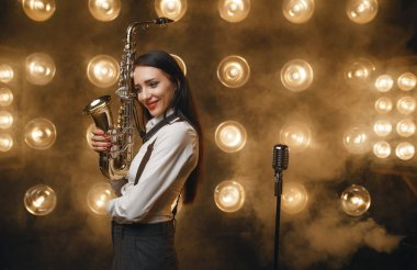 Female saxophonist poses with saxophone on the stage with spotlights. Jazz performer playing on the scene