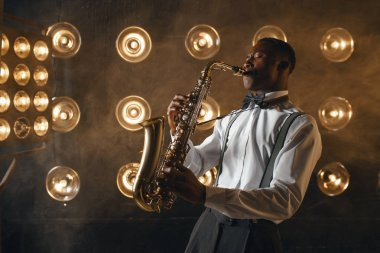 African jazz performer plays the saxophone on the stage with spotlights. Black jazzman preforming on the scene